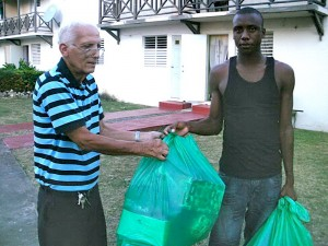 Grandpa Geddes Corrie handing over 2 large bags of gifts to 19 year-old Barbados Defence Force (BDF) soldier Lamar Cummins