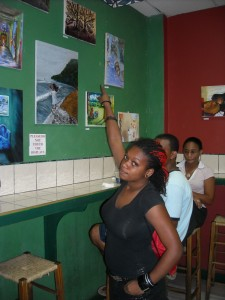 Vanessa Jones pointing at her work by Delicateesen in Ideal Restaurant