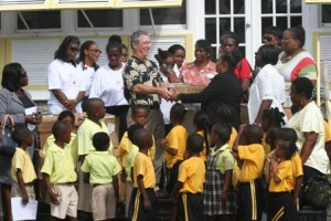 General Manager of the Nisbet Plantation Beach Club Mr. Jamie Holmes delivers the books from Dr. Jan Owens to Director of Library Services on Nevis Mrs. Sonita Daniel in the presence of education officials and students.