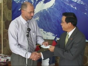 """Minister of State responsible for culture, Honourable Richard Skerritt (left) accepts the """"generous donation"""" from His Excellency Rong Chuan Wu"""