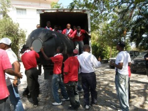 Digicel unloads a water tank for people living in a camp at the Prime Minister's office