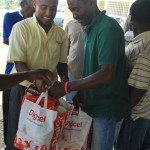Digicel Sponsorship Manager JR Eliacin presents a care pack to a representative of the Haiti Football Federation