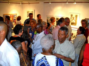 Pauline Beckles in a blue and white dress backing camera while Billy Gollop chats with her (right corner of shot) at Bridgetown Gallery
