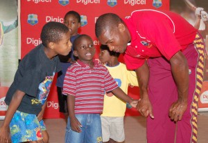 David Bernard listens to one of the boys talking about his love for cricket - Adrian Narine photo, courtesy DigicelCricket.com