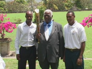 His Excellency the Governor General, Sir Cuthbert Sebastian holds the Queen's Baton. He is flanked by Kim Collins (left) and Jason Rogers