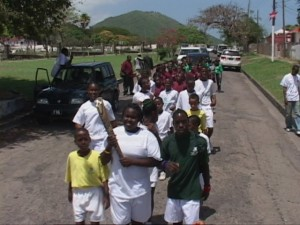 Special Olympic athletes and students from the Tucker Clarke Primary School run with the Baton
