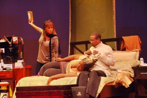 """Mary/Endy McKay {left} about to assault her sister Catherine/Nailah Cumberbatch on the lap of Mike/""""Blood"""" Armstrong (All photos courtesy Matthew Murrell & Gale Theatre)"""