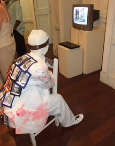 Barbadian & Caribbean heroes on the back of Egungun (Yoruba God of the Dead) as he watches TV - Russell Watson