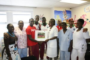 Jerome Taylor presents an autographed West Indies team photo to staff of the Childrens Ward of the Mount St Johns Medical Center - Johnny Jno Baptiste photo and DigicelCricket.com