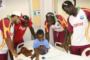 West Indies players Ramnaresh Sarwan, Jerome Taylor, Darren Sammy and Andre Fletcher get video gaming tips from a young patient at the Mount St Johns Medical Center - Johnny Jno Baptiste photo and DigicelCricket.com