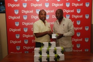 Digicel Sponsorship Manager, Jean Ronald Eliacin, gives the new mobile phones to Vice-President of the Haitian Football Federation, Julio Cadet