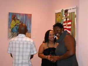 "{SPARMAN CLINIC} Extreme right in glasses - Petra Toyin with patrons, painting on left from Nicholas Barnett and to the right is Ras Akyem's ""Bad Boy"""