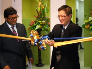 Dr Persaud at left watches on as Jeng Zhang of CIDA cuts the ribbon officially opening the Bajan branch of CaPRI - Caribbean Private Research Investments
