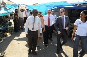 LEFT TO RIGHT - CUSTODIAN OF KINGSTON, STEADMAN FULLER, TAKES COLM DELVES, GROUP CEO OF DIGICEL, AND MARK LINEHAN, DIGICEL JAMAICA CEO, ON A TOUR OF THE MARKET