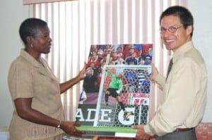 Sports Council Assistant Director of Sports, Mona Alleyne (left) accepting one of the posters from Embassy Deputy Public Affairs Officer Dr. Joseph Schaller