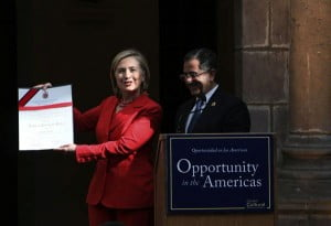 Secretary of State Hillary Rodham Clinton shows a gift given to her by Quito's Mayor Augusto Barrera, right, in Quito, Ecuador, June 8, 2010