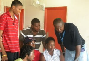 Web design students Xavier Inniss (standing at left), Jamal Als, Betty Jones, Damian Williams, Amanda Nelson (at the computer) and Patrick Yearwood.