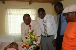 (L to R) Minister responsible for Social Development Hon. Hensley Daniel presents a bouquet of fresh flowers to bedridden Mrs. Josephine France, in recognition of her 100th birthday. He is accompanied by Junior Minister in the NIA Hon. Dwight Cozier and Area representative and Attorney General Hon. Patrice Nisbett while daughter and caregiver Ms. Serita France (extreme right) looks on