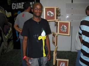 Romal next to some sculpted versions of his cartoon character