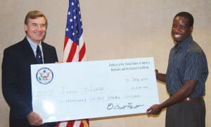 Charge D'Affaires Dr. Brent Hardt (left) presenting winner Jason Blounte (right) with his cheque.