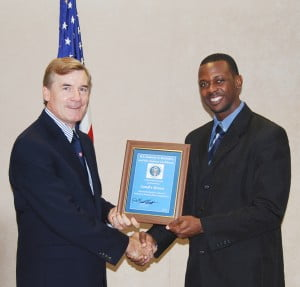 Charge D'Affaires Dr. Brenth Hardt presenting Zandre Bowen with his certificate.