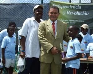 Ambassador Bello presents trophy to participant as tennis Coach Ludis Francis looks on.