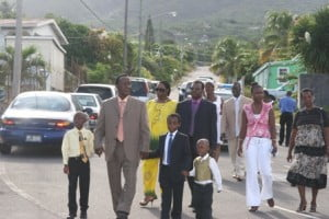 Nevisian Hero and Honouree Mr. Uhral St. Clair Swanston with his grand children in hand lead other family members to the site of the road renaming ceremony in his honour at the bottom of Zion Hill