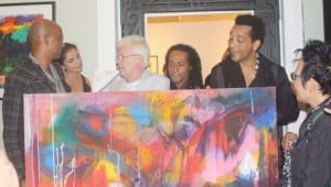 3 Canal receiving a painting at the opening reception of Rex Dixon's Seventeen Colours Art Exibition