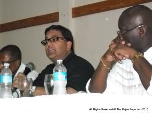 Professor Persaud using the mic, seated between the Co-Chairs of that night's session