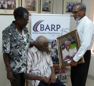 Jean Springer looks on as James Sisnett admires the photograph being presented by BARP President Ernest Batson