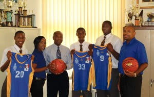 KFC's Marketing Coordinator, Shekelia Barrow giving one of the donated basketballs to Combermere's Principal, Mr.Vere Parris while from (L_R) shooting guards Tionne Bostic and Armani Prescod look on with big center Kareem Tyrell and coach, Stuart Mayers