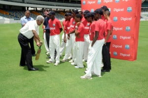 Sir Garfield Sobers shows young cricketers how to bat at the launch of the Digicel Youth Cricket Programme