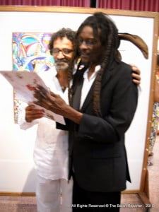 """Ras Akyem gives an autograph for Cuban artist Leandro Soto (who designed the set for """"It So Happen"""")"""