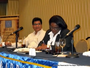 With BCCI's Sr VP looking on, Ms Mottley takes a moment to fine tune the speech before stepping up to the lectern