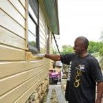 Wadadah President and Chivas Regal Ambassador, Sydney Cox, proudly applying paint to the Ocean View Road, Spooner's Hill, St. Michael home of Everton Brathwaite