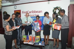 Soroptomist International of Barbados president Sisporansa Stanford (third left) and Mark St. Hill, CIBC FirstCaribbean's Country Head for Barbados peruse some of the educational materials donated by the bank to the new resource centre at the Girls Industrial School along with from left: Judith Toppin, Tammy Bryan, Pansy Griffith and Daniele Maycock of Soroptomist International; Carolyn Lewis, Head of HR Barbados, CIBC FirstCaribbean; and Deidre Perch, Government Industrial School.