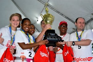The triumphant Digicel 4G CEO Challenge team, led by CEO designate, John Gilvarry (centre). Other members of the team pictured here are Ciaran Burke (right), Digicel CFO; Nadia Alleyne (fourth from left), Legal Counsel; Marketing Executive, Shakida Grant (third from left); Digicel Musical Ambassador, Malissa Alanna (left); and Marketing Executive, Randy Howard (hidden, second from left). Presenting the Challenge Trophy to the team is Commercial Director, Alex Tasker (second from right).