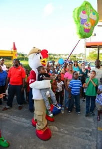 Some children needed a little help from KFC's mascot Chicky to really give the piñata a good whack.