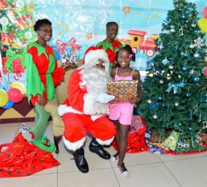 "Santa Claus got a head start on Wednesday delivering gifts to the children of KFC's Chicky Club at KFC Warrens. Here he gets some help from two ""elves"" with choosing the right gift for little Caia Blackman."