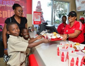The Children of the Eagle Hall Primary Special Unit enjoyed some KFC and had a wonderful time during their tour of Sheraton Mall yesterday. Here, Tamico Chase receives his So Good meal from Joan Breedy, Customer Service Team Member as Martin Greene and teacher of Eagle Hall's Special Unit, Ms. Cindy Brown look on.