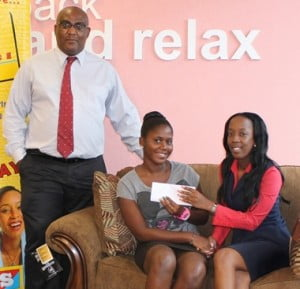 Winner of the second draw in the KFC/Courts Makeover your Home for the Holidays promotion, Ms. Shakeea Boyce (centre) is congratulated by KFC Marketing Coordinator Ms. Shekelia Barrow, and Simon Prince, Director of Electrical Purchasing - Unicomer Barbados Limited.