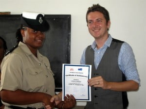 Governor's Staff Officer Tom Regan presents a certificate to new prison officer Logun O'Brien.