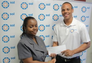 Kirk King, Sales and Marketing Manager Sol (Barbados) Ltd, presents Stephanie Kothdiwala with the cheque for her winning photograph of Cherry Tree Hill.