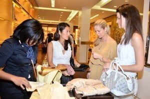 At left Louis Vuitton's Sales Associate Dana Ward, shows customers the new line of evening pochettes which form part of the store's beautiful new bags, shades, scarves available for the festive season.