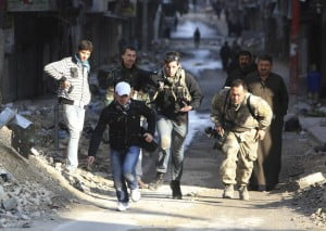 Journalists run along a street in Aleppo's district of Salaheddine on Dec. 29, 2012. REUTERS/Muzaffar Salman