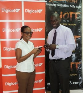 Digicel Marketing Executive, Shakida Grant (left) and Acting Advertising Manager of the Starcom Network, Vilmore Johnson, testing the official text line for the Digicel/HOTT Carnival Safari text promotion.