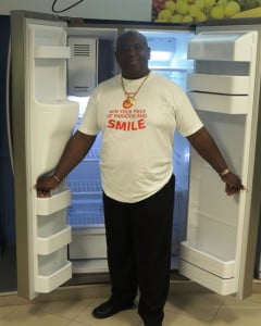 Ready to stock! Jeffrey Cox, week 5 winner in Digicel's Win a Piece of Paradise and Smile promotion, poses with his brand new Samsung refrigerator.