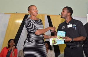 Ricardo Cole, YUTE Programme participant was in high spirits as he received his personal copy of Services For Urban Youth from Ms. Maureen Webber, YUTE Programme Manager