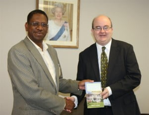 William Hinds (LEFT)  presenting a copy of his book to British High Commissioner Paul Brummell