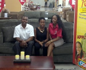 KFC Marketing Coordinator, Ms. Shekelia Barrow and Mr. Davidson Ishmael, General Manager of Courts Bridgetown trying out the new furniture with winner Ms. Ashley Moore (centre).